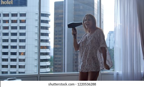 Young funny joyful woman in pajamas drying hair dances sings sons by panoramic window at home