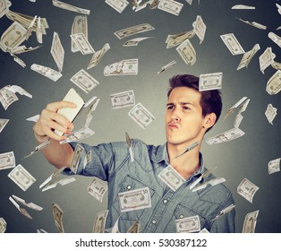 young funny looking man taking pictures of him self with smart phone under money rain