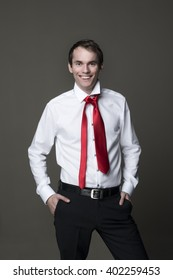 Young funny man with bad red tie smiling
