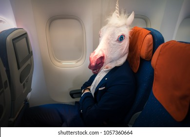 Young funny man in comical mask travels by plane. Unusual passenger in elegant suit sits alone inside the aircraft and ready to take off. Freaky traveler in air voyage. Unicorn enjoys his flying