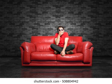 young funny man covering mouth sitting down.