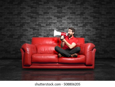young funny man with megaphone, sitting down.