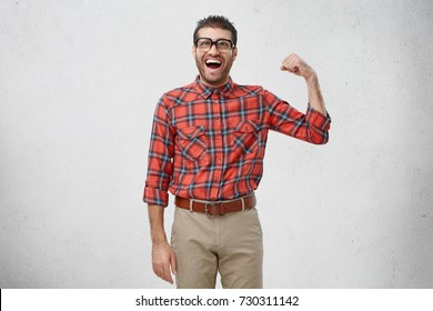 Young funny man wears spectacles and checkered shirt, shows biceps after first training in gym, isolated over white background. Clumsy male geek boast of his strength, shows strong man`s hand