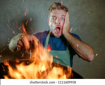young funny and messy home cook man with apron in shock holding pan in fire burning the food in kitchen disaster and unskilled unexperienced terrible home cook at domestic cooking mess