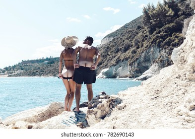 Young funny nudist couple showing ass to the camera on the nudism beach.