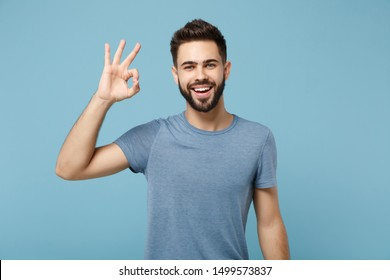 Young funny smiling handsome man in casual clothes posing isolated on blue wall background, studio portrait. People sincere emotions lifestyle concept. Mock up copy space. Showing OK gesture