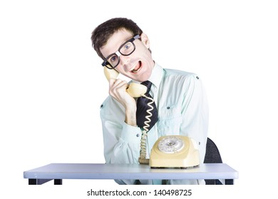 Young funny telemarketing businessman sitting at table with retro telephone, annoying call center clerk concept, white background