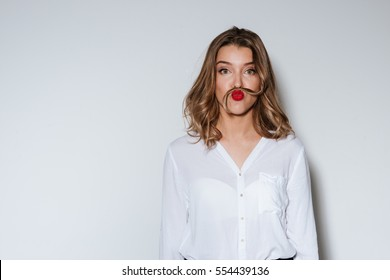 Young funny woman making mustache with a long strand of her hair in a humorous way over white background