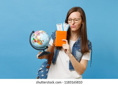 Young funny woman student in glasses with backpack holding world glove, passport, boarding pass tickets isolated on blue background. Education in university college abroad. Air travel flight concept