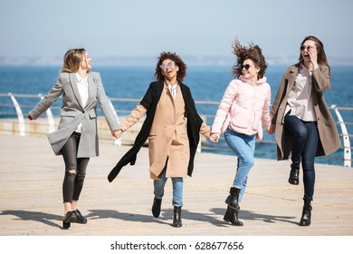 Young funny women walking and jumping near seaside