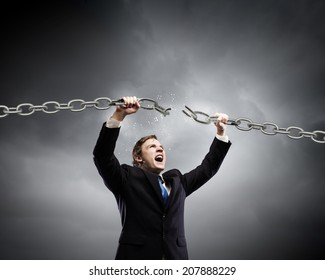 Young furious businessman breaking metal chain with hands