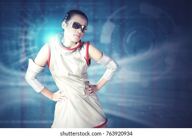 Young futuristic woman wearing a silver latex costume and glasses while standing with virtual screen in the background