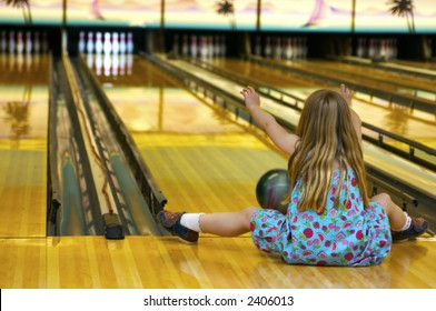 A young gal at the bowling alley - playing 'crazy bowl' - a game where you do a variety of different ways of rolling the ball down the alley - like with your feet etc.