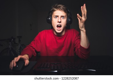 Young gamer is angry with the bad team play in the video game. Portrait of an emotional gamer playing online video games at home on the computer, raising his hands up from surprise.