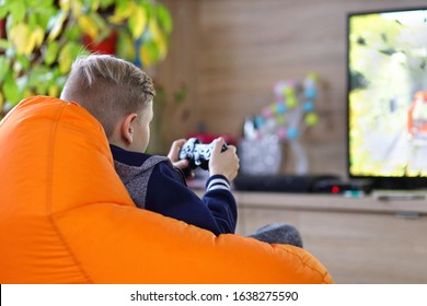 Young gamer boy playing online car racing game on new console at home tv – little kid sitting in gamer bean bag chair having fun streaming online – new technology game trends and entertainment concept