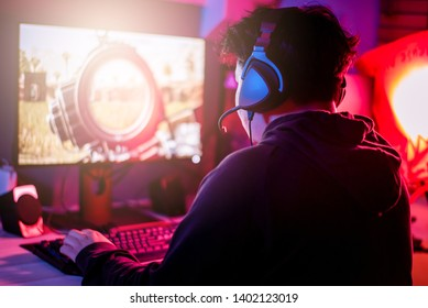 Young gamer playing game with computer PC and wearing headphone.
