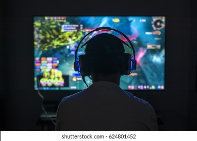 Young gamer playing video game wearing headphone.