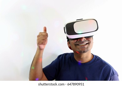 Young gamer thumbs up while using virtual reality goggles