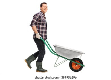 Young gardener pushing a wheelbarrow and looking at the camera isolated on white background