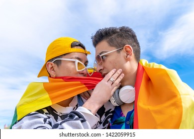 young gay couple kissing, wearing a gay pride flag