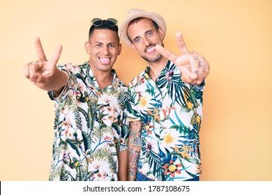 Joven pareja gay de dos hombres con sombrero de verano y camisa hawaiana sonriendo con la lengua mostrando dedos de ambas manos haciendo señal de victoria. número dos.