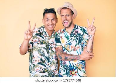 Joven pareja gay de dos hombres con sombrero de verano y camiseta hawaiana sonriendo con la cara feliz guiñando el ojo en la cámara haciendo el signo de la victoria con los dedos. número dos.