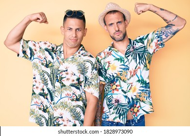 Young gay couple of two men wearing summer hat and hawaiian shirt strong person showing arm muscle, confident and proud of power