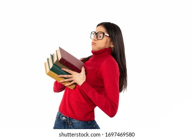 Young geek female student holding bunch of heavy books in two hands, struggling to carry the books, wearing casual red sweater and reading glasses, isolated on white background