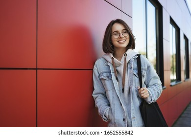 Young generation, lifestyle and education concept. Outdoor portrait of happy girl on her way home after classes, looking sideways dreamy and happy smiling, holding tote bag, lean red building