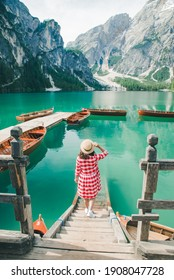 young gentle woman in red checkered dress barefoot walking by wooden stairs of boat station leads to lake. summer vacation