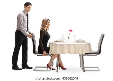 Young gentleman helping his girlfriend with the chair at a restaurant table isolated on white background