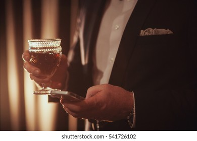 Young ginger bearded man holding a vintage glass with red wine against the light. black on background. guy looking in the phone