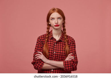 young ginger female looks upwards at copy space , keeps her hands crossed on chest with negative, sad facial expression. Isolated over pink background