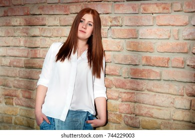Young ginger girl daydreaming by brick wall.
