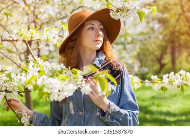 Young ginger hair woman in hippie gypsy jeans jacket, brown hat near white tender blossoming sacura cherry tree. Fairy dreamlike mood of spring. Beautiful romantic freedom travel lifestyle.
