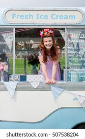 Young ginger haired lady with facepaint smiling wearing vintage dress and flower headband stood in ice cream van. Portrait image with text space