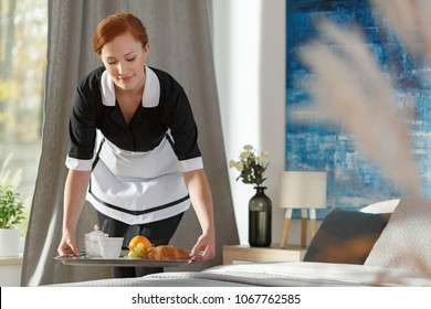 A young, ginger housemaid delivering breakfast to a hotel bedroom