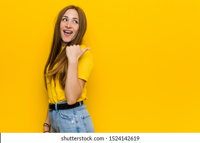 Young ginger redhead woman points with thumb finger away, laughing and carefree.
