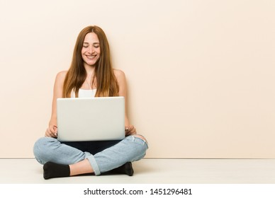 Young ginger woman sitting on her house floor laughs and closes eyes, feels relaxed and happy.