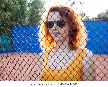 Young ginger woman in sunglasses with a bag on a sports ground, view through the grid