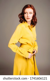Young ginger woman in yellow shirt dress. Female bright look, lemon casual style. Fashion portrait on neutral background.