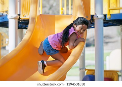 Young girl 5 year old climbing up a slide in a kids playground and enjoying the physical challenge