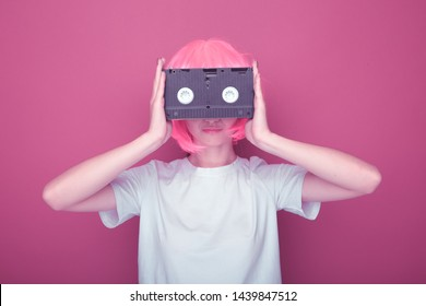 Young girl 90s and VHS cassette on pink