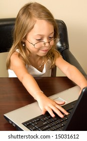 A young girl about 6 pretends to be busy at her notebook computer while wearing glasses too big for her head.