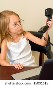 A young girl about 6 pretends to be busy at her notebook computer while wearing glasses too big for her head, reacting to the telephone.