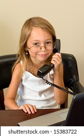 A young girl about 6 pretends to be busy at her notebook computer while wearing glasses too big for her head, talking on a telephone.