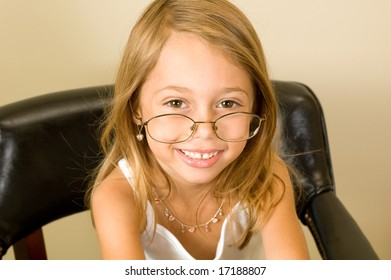 A young girl about 6 pretends to be working while wearing glasses too big for her head.