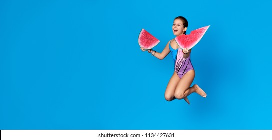 Young girl active jumping up, Studio isolated blue background.Summer concept.