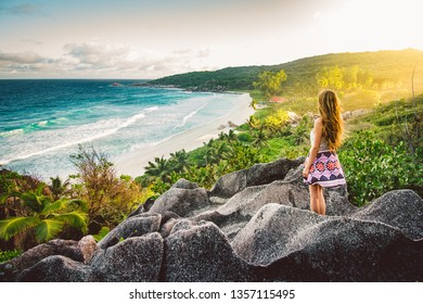 A young girl admiring the view at Grande Anse beach located on La Digue Island, Seychelles