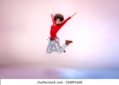 Young girl with afro jumping, flying, dancing in studio.